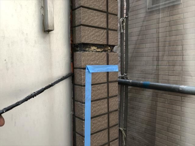 タイル壁面と共用廊下落下防止手摺柵の金属面の境界に打たれたコーキングが劣化していた事が階下の雨漏りの原因だった