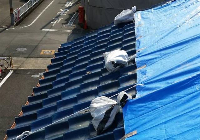 地震のダメージを受けた瓦屋根の軒先へはとても近づくことが出来ずブルーシートを張る範囲は限られる