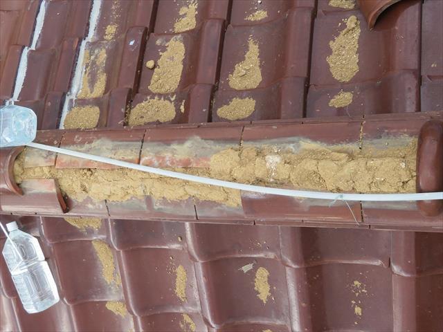 実際に棟瓦(冠瓦)が欠損した被害状態を見ましょう。直下の熨斗瓦の上に盛られた葺き土は、多量の雨に晒されました。 棟瓦(冠瓦)が欠損した部位で、直下の熨斗瓦の上に残存している葺き土から受ける印象は、土と言うより「砂」に近いものです。