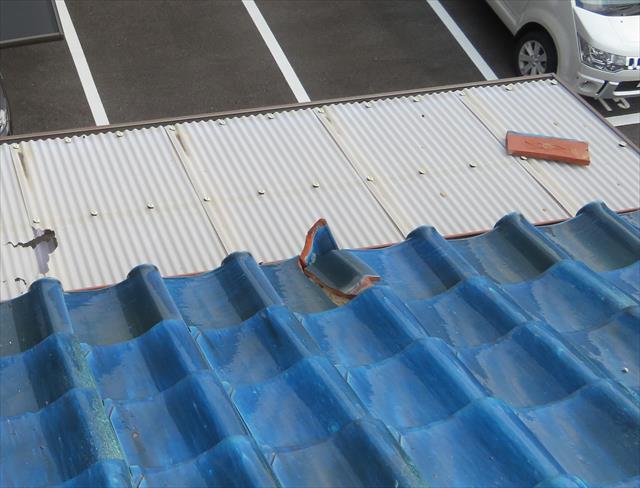 切妻屋根の崩壊した大棟から滑落した熨斗瓦はベランダの波板を割損させた