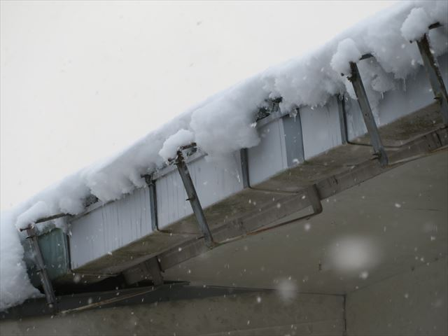 屋根から滑落してくる降雪は軒先の雨どいに負荷をかけている