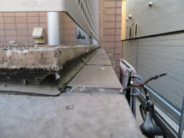 バルコニー外壁の天端とタイルの境目のコーキング劣化によって内部に雨水が侵入してタイルが浮き上がった