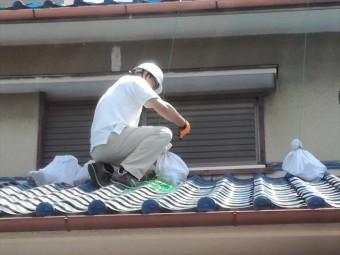 大屋根から垂らしたロープで土嚢袋を結び、ブルーシートを固定する