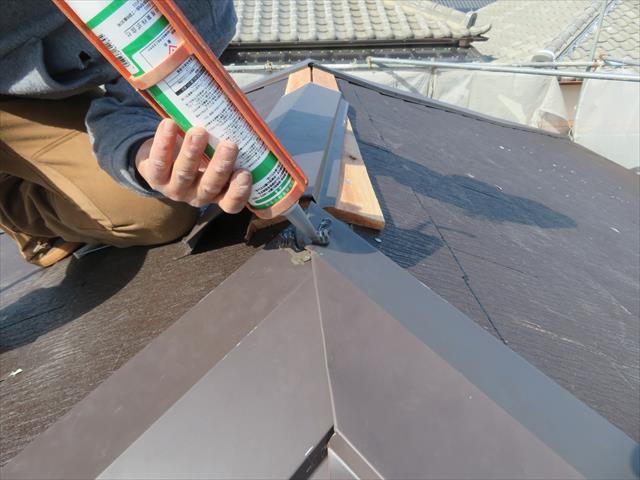 頂上で接合する隅棟には、他方から追い当たってくる隅棟を飲み込ませて(被せ込む)雨仕舞とします。 継ぎ目にはコーキング剤を充填して、棟包み内部に雨水が入らないようにします。
