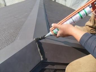 大棟が板金で包まれると最終局面のコーキング充填です。板金の接合部分から雨水が入らないように、必ず行う工程です。