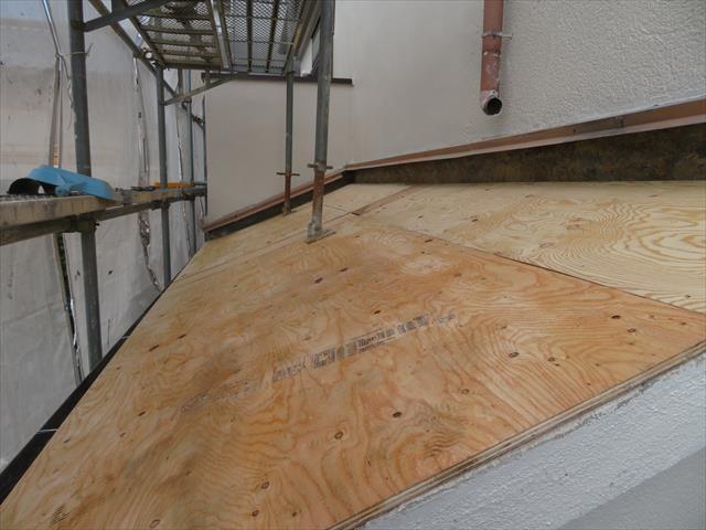 瓦と葺き土をきれいに取り除いた後、構造用合板を下屋根に揚げて行き、野地板の上に敷き詰めて行きます。 元々瓦であった屋根は1坪当たり235kgの荷重が不均一に掛かっていましたので、野地板や垂木は圧縮されて水平水準も不均一になっています。