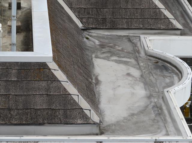 フェンス外側には、垂直のパラペットと床面で出来る空間を化粧し防水するカラーベスト屋根が葺かれています。 カラーベストの先には建物と一体成型されたコンクリート製の雨どいが塩ビシートで防水されていますが、塩ビシート防水はパラペット立上り全体まで入っている