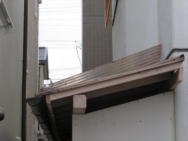 ビル裏手の木製納屋の波板屋根が台風21号でめくれあがっている事が判ります