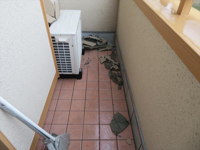 台風21号の強風はモルタル外壁を破壊し、その破片は近隣のお宅のバルコニーまで達していて散乱していた