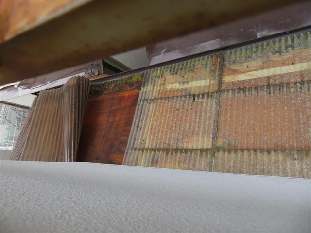ビル裏手納屋の波板屋根が台風21号の強風でめくれあがっている