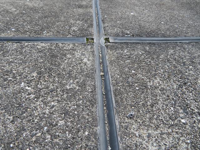 屋上土間のシンダーコンクリートは平面で雨水の影響を強く受けるので、30年を減るとセメント成分が流れ出し、砂粒が露出した荒れた状態になっている