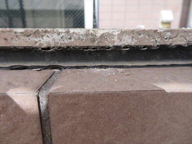 バルコニー天端のシール効果が剥落しタイル内側に雨水が侵入して下地との接着効果を落とすことでタイルは浮き上がる