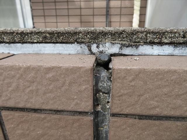 バルコニー外壁の天端(頂部)には、重量鉄骨躯体と外壁本体のALC、外壁タイルの落差を埋めるコーキングがある。