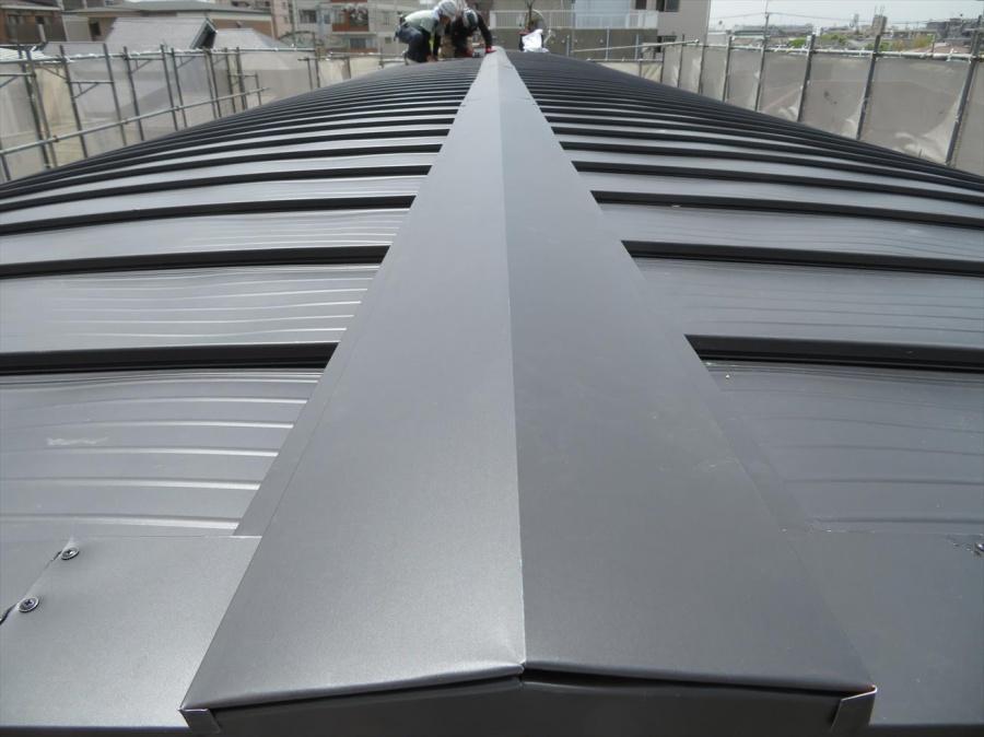 カバー工事で仕上がったJFEライン立平333をアーチ型屋根の大棟包み板金が仕上がった状態とまっすぐに真が通った