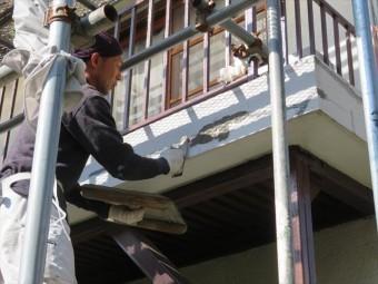 モルタル外壁に生じた太いクラックには接着剤入りのモルタルを左官作業で充填していく