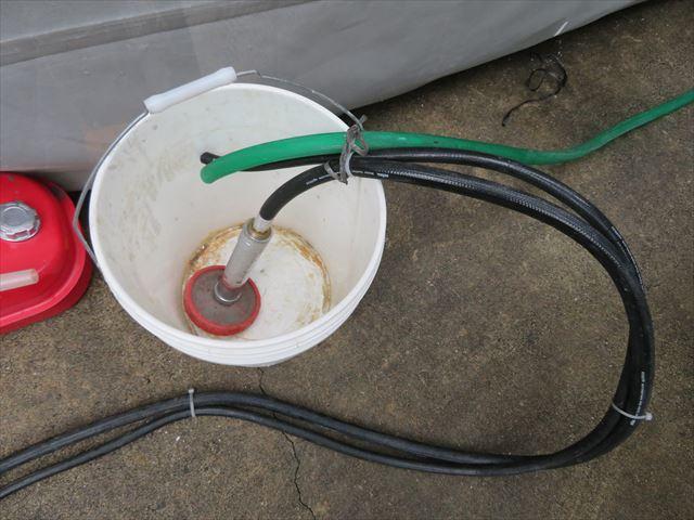 高圧洗浄機に供給する水道水を溜めるバケツには水道水供給ホース、サクションホース、循環ホースが固定されている