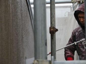 リシン吹き付け仕上げの外壁面の汚れを剥がし落とす強力な高圧洗浄作業