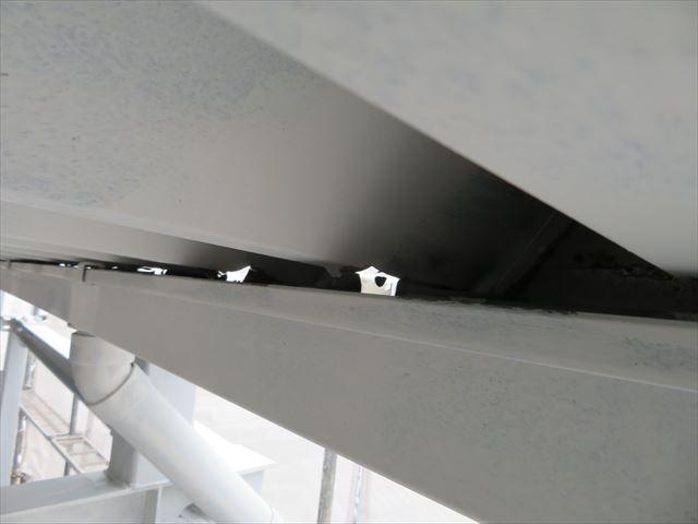 折板屋根の下部に設置された軒樋は、竪樋から遠ざかるにつれて雨水の滞留量が多くなっている異常な状態です
