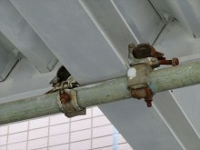 H型鋼にクランプを利用して足場の単管が固定されている部分も1箇所ずつ緩めて塗装する