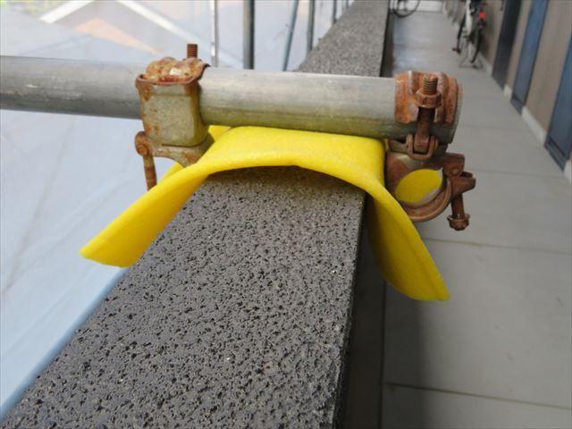 共用廊下の外壁を単管とクランプを使って固定することで足場は建物とともに強固に自立するが外壁塗装がしにくい箇所になってしまう