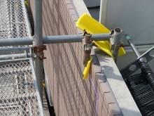 バルコニー外壁に単管とクランプで足場を補強させているが、外壁塗装をしにくい場所になっている
