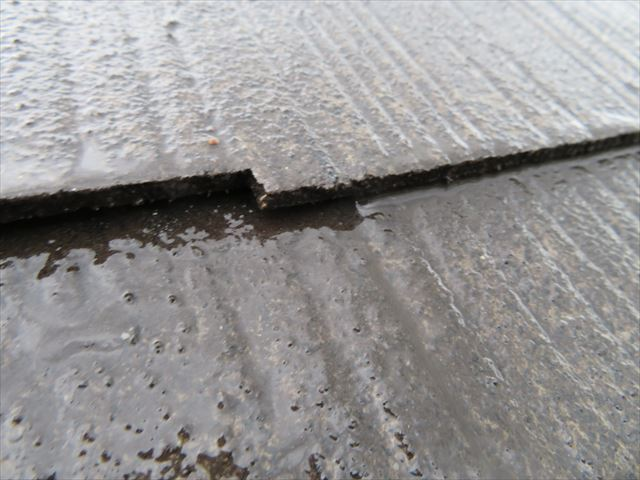 高圧洗浄中のコロニアルの左端を持ち上げると、屋根材の継ぎ目の水分が切れていくことが解る