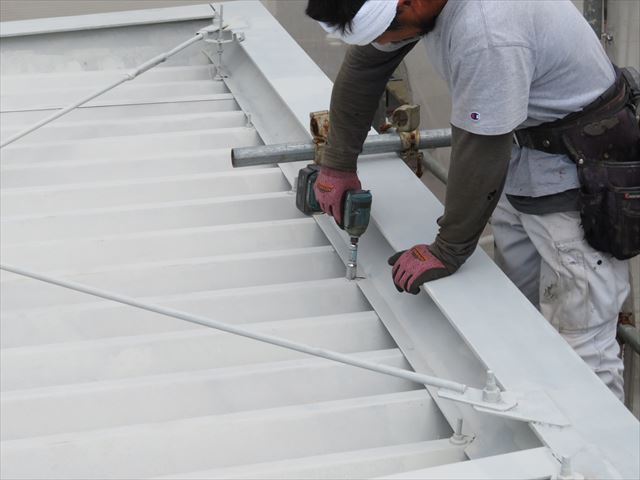 折板屋根の下に設置された軒樋はボルトナットで固定されていて、経年劣化や自然現象で勾配が変化することはない