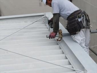 吊り金具で折板屋根の上から吊り下げられている軒樋を下げるには屋根上のナットを緩めなければならない