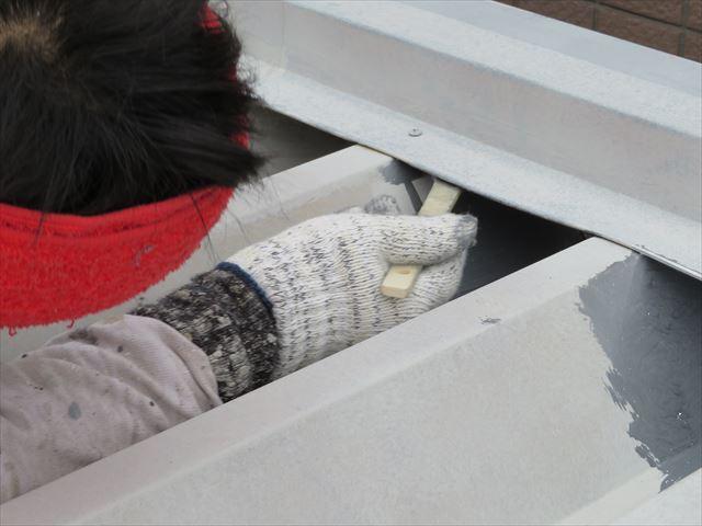 H型鋼の中に差し込まれた折板屋根の端部はハケで奥深く、上面もコツコツ塗って行く