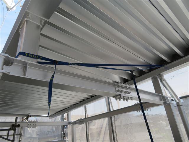 雨どい(軒樋)の吊り金具にラッシングベルトをかけて絞って行くと、雨どい(軒樋)がH型鋼から距離ができることになる修正作業