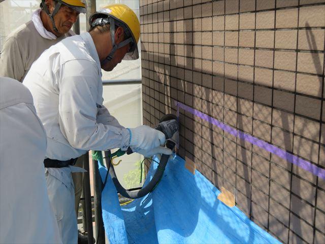 外壁タイルの目地はサンダーを使って切断していくが、集塵機で粉塵を吸いながら進める