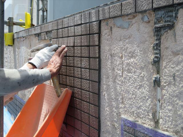 斫られた外壁タイルはすぐに何十キロの重さになるので、ブルーシートだけに頼らず、プラスチックの受け皿で受け止めていく