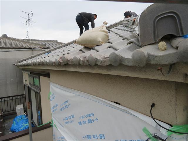 瓦屋根の葺き替え工事が始まるので、ブルーシートを剥がし重しに使っていた土嚢袋も撤去します。