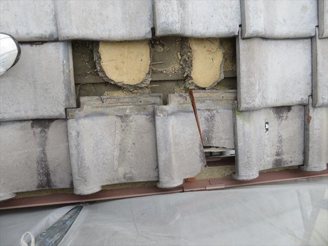 高槻市で台風の二次被害を受けた瓦屋根の軒先マンジュウ瓦を修理するときに内部の葺き土が見えますが、ブルーシートで雨漏り養生していたので、乾いた黄土色をしていることが解ります。