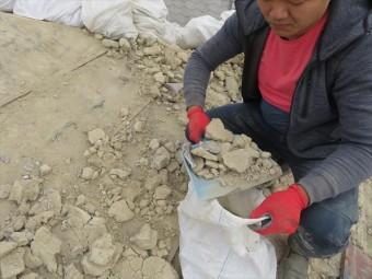 瓦の葺き土は小分けにしながら土嚢袋に詰めて行く