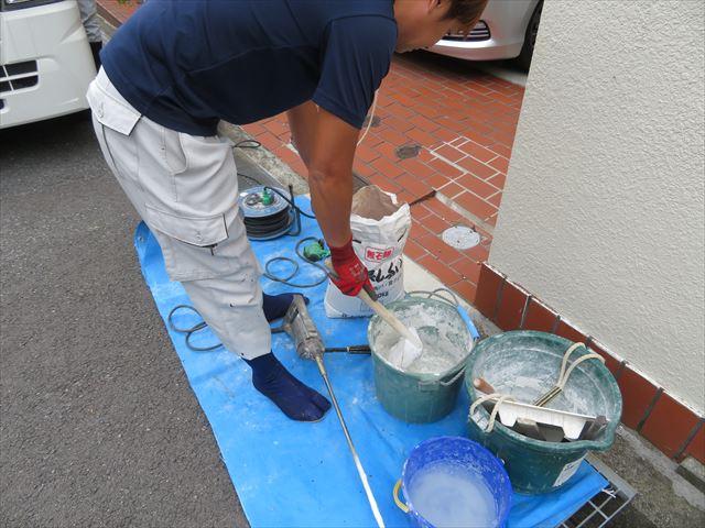 汚損防止用のブルーシートで養生をして漆喰の撹拌作業を開始する。混ざりムラが出ないよう撹拌機を使用します