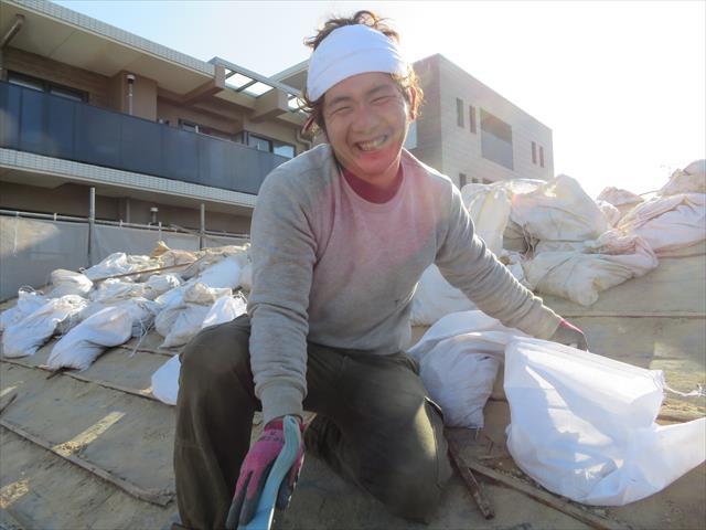 茨木市の震災風災を受けたお宅の屋根の葺き替え工事で、昭和40年から50年代にポピュラーだった和型施釉瓦を下ろしていく職人のゆうき君