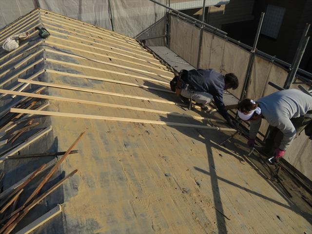 瓦屋根の葺き替えには構造用合板で野地板を補強しますが、張り継ぎ目の強度確保のために、胴縁で下地を作っていきます。
