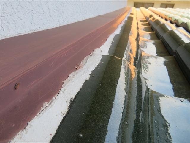 雨仕舞の原則通り、瓦は雨押え板金の内部に飲み込ませて、隙間は漆喰を充填して雨水が内部に入るのを防いでいる