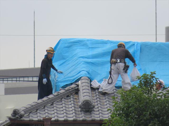 地震で損傷した屋根は職人さんがブルーシートをかけて雨降りに備える