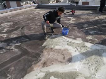 塩ビシート防水工事前に陸屋根表面のシンダーコンクリート土間をカチオン性モルタルでしごき表面を均す
