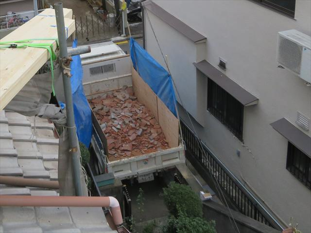 屋根葺き替え工事で出る廃材は、昇降機を使って人海戦術で地上に降ろしていき、ガレージにつけたダンプカーに積み込んで行きます。